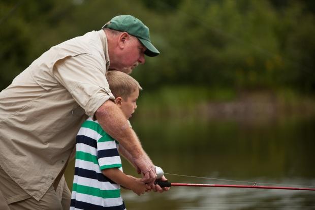 volunteer helping boy fish by David O'Connor